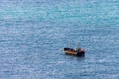 Minimalistic bild av havet med en fiskebåt Blått havsvatten och klar himmel arkivfoto