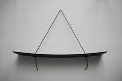 Minimalistic Black hanging shelf. Minimalistic Black shelf hanging on white wall Stock Photo