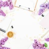 Minimalistic-Blogger oder Freiberuflerarbeitsplatz mit Klemmbrett, Notizbuch, Umschlag, Flieder und Zubehör auf weißem Hintergrun Stockfotografie