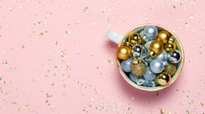 Minimalistic Christmas concept. Christmas decorations in cup on pink background. Top view, flat lay. Copyspace fot rext royalty free stock photos
