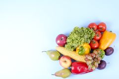 Minimalistic composition with buch of fresh organic mixed fruits and vegetables on light blue background. stock photo