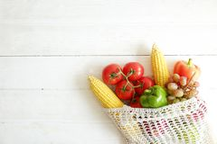 Minimalistic compositions with bunch of different fruits and vegetables in recyclable string sack. royalty free stock photos