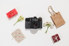 Minimalistic flat lay composition with retro camera, red gift boxes, craft bag, canvas bag with red heart shapes and. Spring field flower on white background stock image
