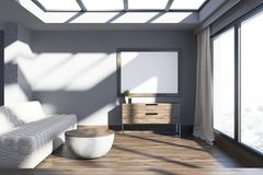 Minimalistic gray living room, sofa and poster. Loft living room interior with gray walls, a sofa, a round coffee table and a large poster hanging above a chest Royalty Free Stock Image