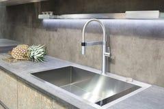 Minimalistic Innenarchitektur der modernen Stahlgrau-Küche mit Mischer und Ananas stockbilder