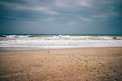 Minimalistic landscape of empty beach, dark storm clouds stock photos