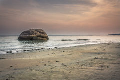 Minimalistic landscape at tropical beach during sunset with big round stone in water Royalty Free Stock Photo