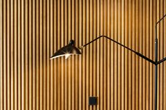 A minimalistic lighting element in the interior. Lamp made of metal against the background of wooden panelsю Royalty Free Stock Photography