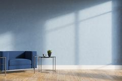 Minimalistic living room, blue armchair. Minimalistic living room interior with blue walls, a wooden floor, a soft blue and silver armchair and a tiny coffee Stock Image