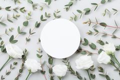 Minimalistic mockup of white flowers and eucalyptus leaves on gray table top view. Flat lay style. Minimalistic mockup of white flowers and eucalyptus leaves on royalty free stock photos