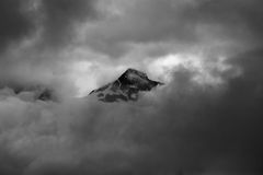 Minimalistic monochrome image of mountain peak shrouded in clou Royalty Free Stock Photo