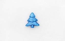 Minimalistic photo of blue toy tree on real snow at winter day. Royalty Free Stock Image