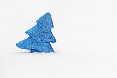 Minimalistic photo of blue toy tree on real snow at winter day. Stock Image