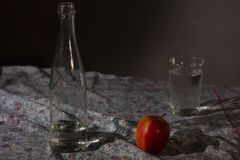 Glass and bottle with clear water and red apple stock photos
