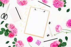 Minimalistic redete Arbeitsplatz mit Klemmbrett, Notizbuch, purpurroten Rosen, Ranunculus und Zubehör auf weißem Hintergrund an F Stockbild