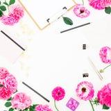 Minimalistic redete Rahmenarbeitsplatz mit Klemmbrett, Notizbuch, purpurroten Rosen und Zubehör auf weißem Hintergrund an Flache  Stockbild
