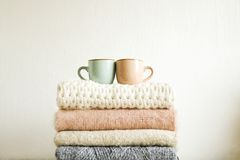 Minimalistic rustic composition with stacked vintage knitted sweaters and cup of coffee on white wall background. stock images