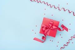 Minimalistic skład z czerwonym prezenta pudełkiem, serpentyną i confetti na błękitnego tła odgórnym widoku, 8 dodatkowy ai jako t Obraz Stock