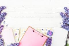 Minimalistic skład z schowkiem, notatnikiem, lilymi kwiatami, prezenta pudełkiem i akcesoriami na drewnianym tle, Mieszkanie niea Fotografia Stock