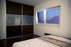 Minimalistic sovrum med det stora inbyggde kabinettet Arkivfoto
