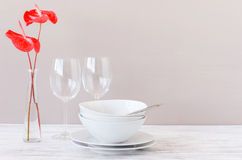 Minimalistic table setting with plain crockery and red flowers Stock Image