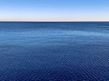 Minimalistic-Wasseroberfläche mit blauem Meerblickhorizont und klarem Steigungshimmel stockfotos