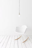 Minimalistic white interior. Modern plastic rocking chair on wooden plank floor against white wall, simple lamp above Royalty Free Stock Photography