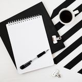 Minimalistic workspace with book, notebook, pencil, cup of coffee on striped black and white background. Flat lay style Top view. Stylish minimalistic workspace stock images