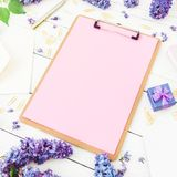 Minimalistic workspace with clipboard, envelope, pen, lilac flowers and box on white background. Flat lay, top view. Freelancer or Stock Photography