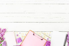 Minimalistic workspace with clipboard, notebook, pen, lilac, ring box and accessories on white rustic background. Flat lay, top vi Royalty Free Stock Photo