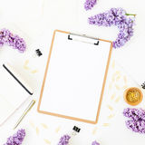 Minimalistic workspace desk with clipboard, notebook, lilac and accessories on white background. Flat lay, top view. Beauty or wed Royalty Free Stock Image