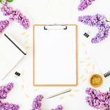 Minimalistic workspace desk with clipboard, notebook, pen, lilac and accessories on white background. Flat lay, top view. Beauty b. Minimalistic workspace desk stock photo