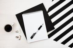 Minimalistic workspace med boken, anteckningsbok, blyertspenna, kopp kaffe på randig svartvit bakgrund Sikt för lekmanna- stil fö royaltyfri bild