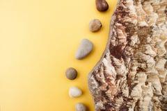Minimalistic-Zusammensetzung von Seekieseln auf einem hellen gelben backg Lizenzfreie Stockbilder