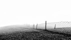 Minimalistic zwart-witte achtergrond van een getelegrafeerde omheining in mistige en nevelige weersomstandigheden royalty-vrije stock afbeelding