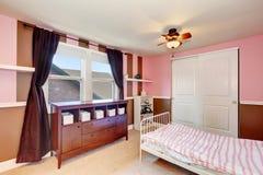 Minimalisticontwerp van kid& x27; s slaapkamerbinnenland met roze accentmuren royalty-vrije stock afbeeldingen