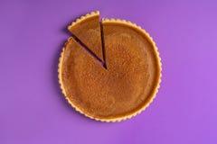 Minimalistisch beeld van een pompoenpastei, met één gesneden stuk en gescheiden, op een purpere achtergrond Hoogste mening Tradit stock foto