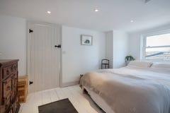 Minimalistische die plattelandshuisjeslaapkamer in wit wordt verfraaid royalty-vrije stock afbeeldingen