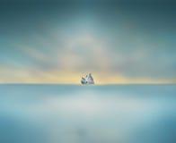 Minimalizmów gołębie siedzi na dużej skale po środku morza Zdjęcia Royalty Free