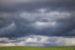 Minimalizm fotografia dramatyczne chmury nad zielenieje pole obraz royalty free