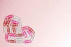 Minimalny pojęcie Kierowy symbol robić materiały klamerki na różowym tle Mieszkanie nieatutowy, odgórny widok zdjęcie stock