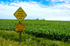 Minimum Maintenance Road. Sign with a farm landscape in the background Stock Image
