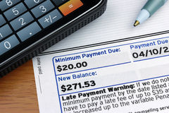 Minimum Payment Due. A detail of a credit card statement highlighting Minimum Payment Due, Payment Due, and New Balance, with a touchscreen calculator Stock Photo