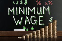 Minimum Wage At Blackboard. Behind Stacked Coins royalty free stock image