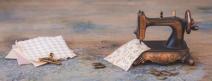 Mininähmaschine der Weinlese mit Scheren, Knöpfen und Gewebe auf rustikalem Hintergrund, Fahne lizenzfreie stockfotos