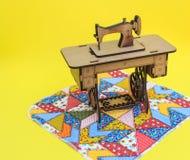 Mininähmaschine, hergestellt vom Holz, auf einer Patchworkwolldecke, mit gelbem Hintergrund stockbild