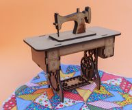 Mininähmaschine, hergestellt vom Holz, auf einer Patchworkwolldecke, mit gelbem Hintergrund lizenzfreie stockfotos