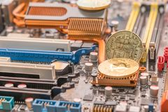 Mining btc crypto cash. Two bitcoin on radiator of desktop computer mainboard.  stock image