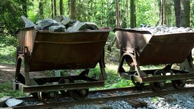 Mining cart with stones. Old and abandoned mining cart in forest stock video