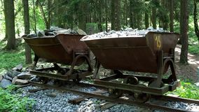 Mining cart with stones. Old and abandoned mining cart in forest stock footage